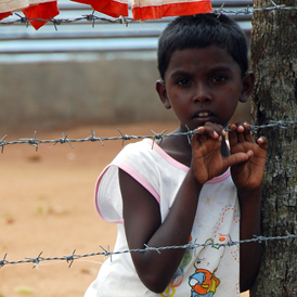 A young Tamil boy stands behind a barbed-wire fence in the Menikfam Vanni refugee camp located near the town of Chettekulam in northern Sri Lanka