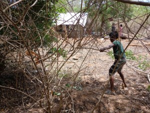 Rajinis son clearing the jungle around their home