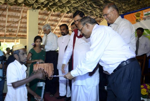 Indian Consul General V.Mahalingam handing over housing documents to a beneficiary to mark the inauguration of the second phase of the Indian Housing project for internally displaced people at a school in Periyamadhu in Mannar district on Tuesday. Photo: R.K.Radhakrishnan