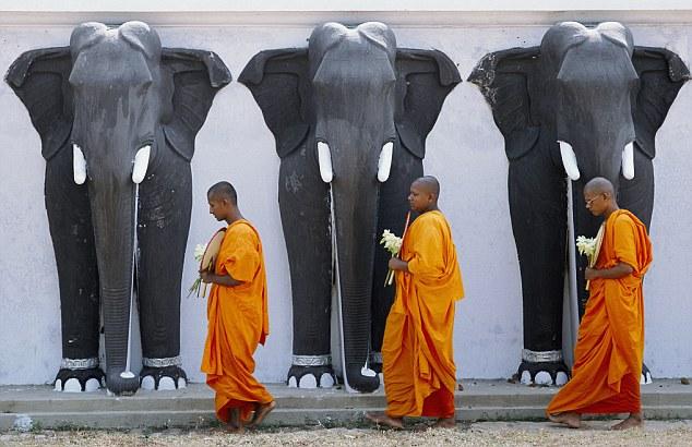 Three Buddhist monks walking past elephant statues