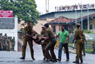 Sri Lankan inmates shout from a roof of a prison building as prison guards carry an injured colleague, foreground right, outside a prison in Colombo, Sri Lanka, Friday, Nov. 9, 2012. Sri Lankan security forces engaged in a gunbattle Friday night with rioting prisoners who appeared to have briefly taken control of at least part of a prison in Colombo. Officials said at least 13 people were wounded in the violence, with several deaths. (AP Photo/Gemunu Amarasinghe)