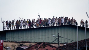 Sri Lankan inmates display guns, throw stones and shout slogans from a roof of a prison in Colombo, Sri Lanka, Friday, Nov. 9, 2012. Sri Lankan security forces engaged in a gunbattle Friday night with rioting prisoners who appeared to have briefly taken control of at least part of a prison in Colombo. Officials said at least 13 people were wounded in the violence with several fatalities. (AP Photo/Gemunu Amarasinghe)