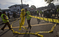 Police officers cordon off an area where a bullet-ridden three-wheeler was used by inmates for their unsuccessful escape attempt, near the entrance to a prison in Colombo, Sri Lanka, Saturday, Nov. 10, 2012. A shootout between rioting prisoners and security forces at the prison killed at least 16 inmates, while police said Saturday that they arrested five prisoners who had managed to escape. (AP Photo/Gemunu Amarasinghe)