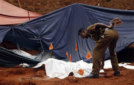 A police officer covers part of a dead body at a building site in Matale, a central town 142 km (88 miles) from the capital, Colombo, December 16, 2012. REUTERS/Dinuka Liyanawatte