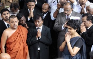 Chief Justice Shirani Bandaranayake, second right, receives blessings of Buddhist Monks and Clergy, before leaving the court complex to appear before a Parliamentary committee to answer impeachment charges in Colombo, Sri Lanka on Dec. 4, 2012.