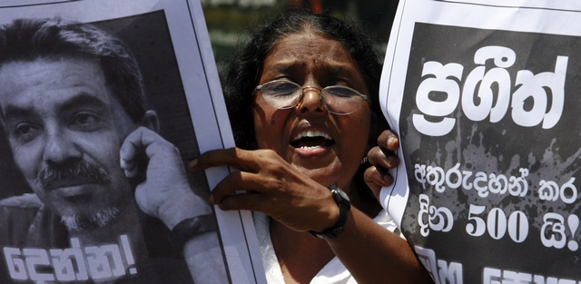 A member of the Free Media Association shouts slogans in front of an image of missing cartoonist and columnist Eknaligoda in Colombo