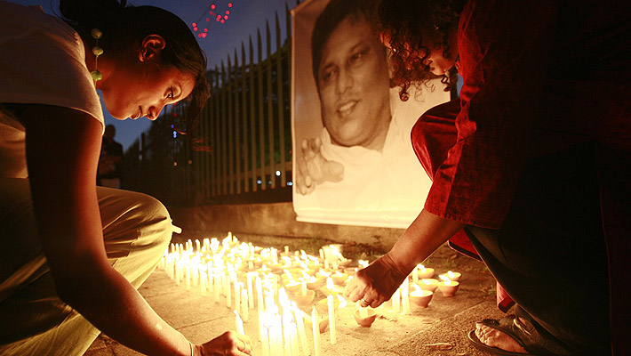 Two women light candles at a vigil on the first anniversary of the murder of Sri Lankan journalist Lasantha Wickrematunga in Colombo