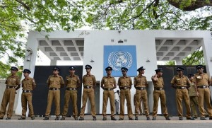 Sri Lankan police officials stand guard outside the United Nations office in Colombo on August 26, 2013
