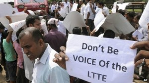 Sri Lankans hold placards while blocking a train carrying Channel 4 journalist Callum Macrae