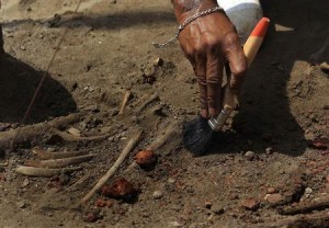 A police officer uses a brush to excavate a human skeleton at a construction site in the former war zone in Mannar