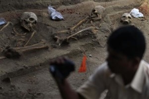 A police officer takes a video of human skeletons at a construction site in the former war zone in Mannar