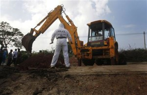A police officer watches as an excavator digs up skeletons at a construction site in the former war zone in Mannar