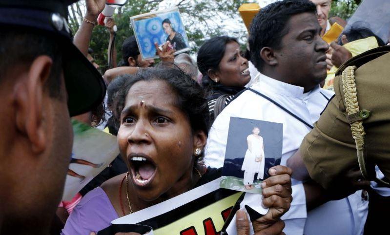 Sri Lankan policemen try to control ethnic Tamil people, in Jaffna, northern Sri Lanka, Nov.15, 2013.