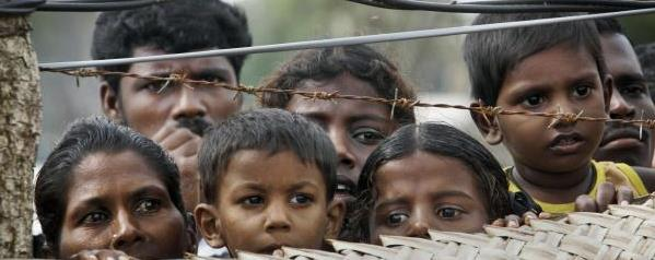 internally_displaced_sri_lankan_tamil_civilians_peep_from_over_a_fence_at_a_camp_for_the_displaced_in_vavuniya
