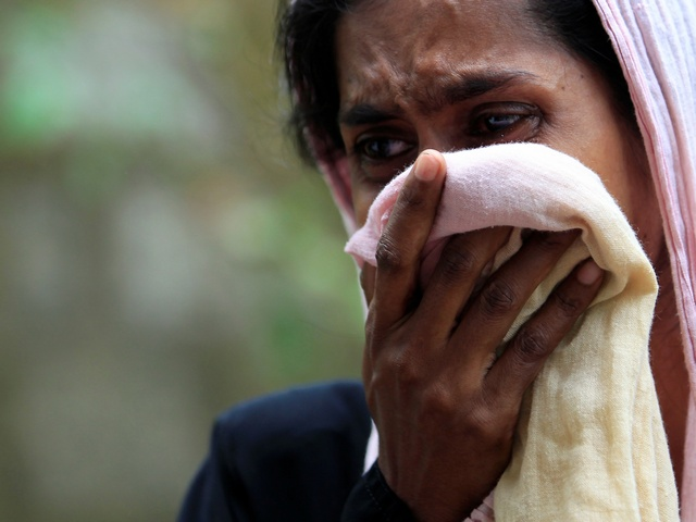 A Muslim woman cries next to her burnt house after a violent attack against Muslims in Aluthgama on June 16, 2014. © 2014 Reuters