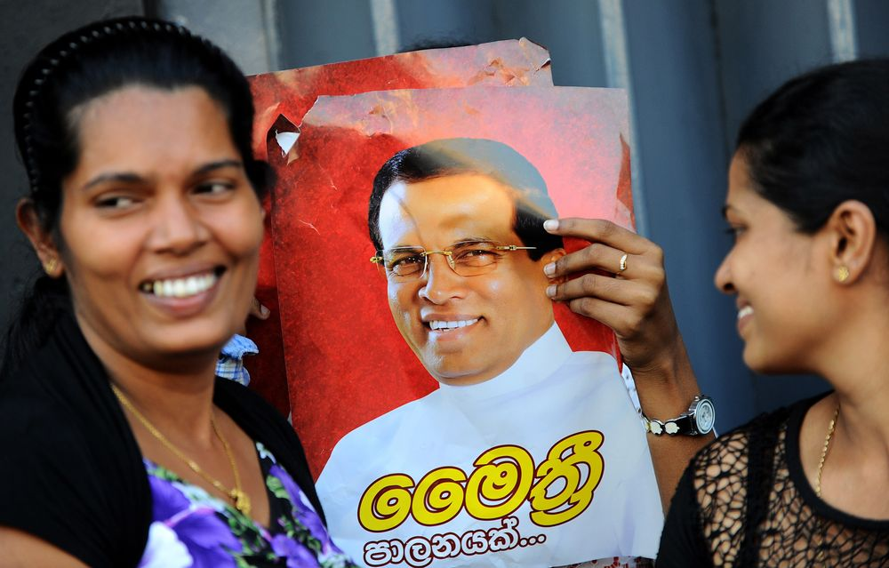 Sirisena supporters hold a campaign poster as they celebrate the the election results in Colombo on January 8, 2015 (S.KODIKARA/AFP/Getty Images)