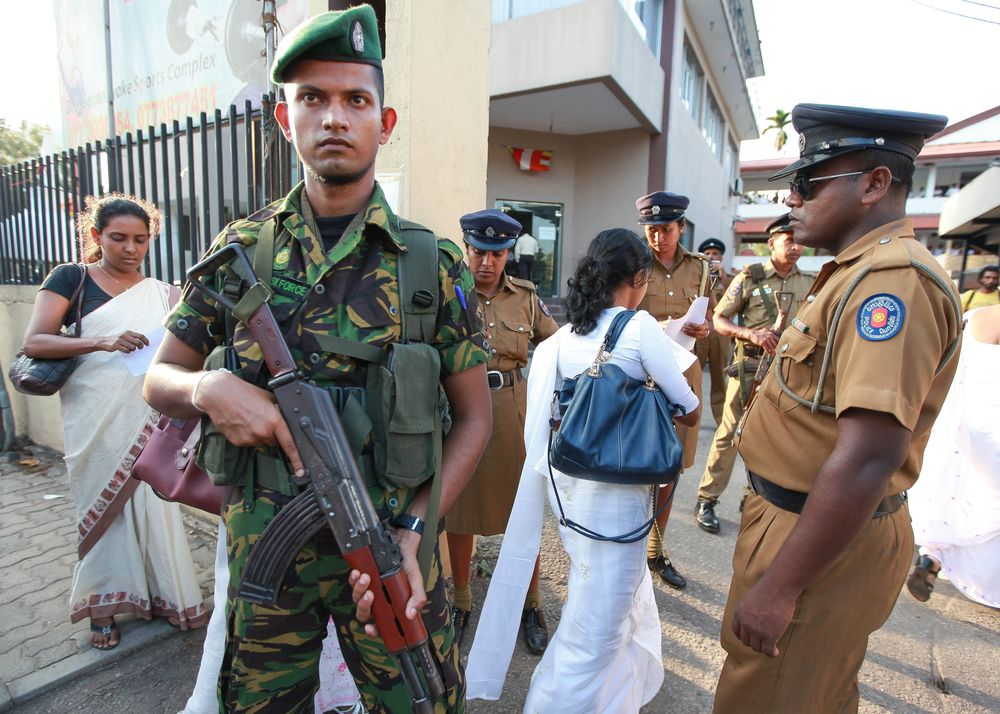 Sri Lankan security forces stand guard at a polling station in Colombo (Chamila Karunarathne/Anadolu Agency/Getty Images)