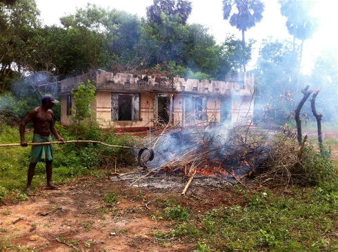 Photo: Amantha Perera/IRIN: A man burns debris in front of a destroyed house in Tellipallai