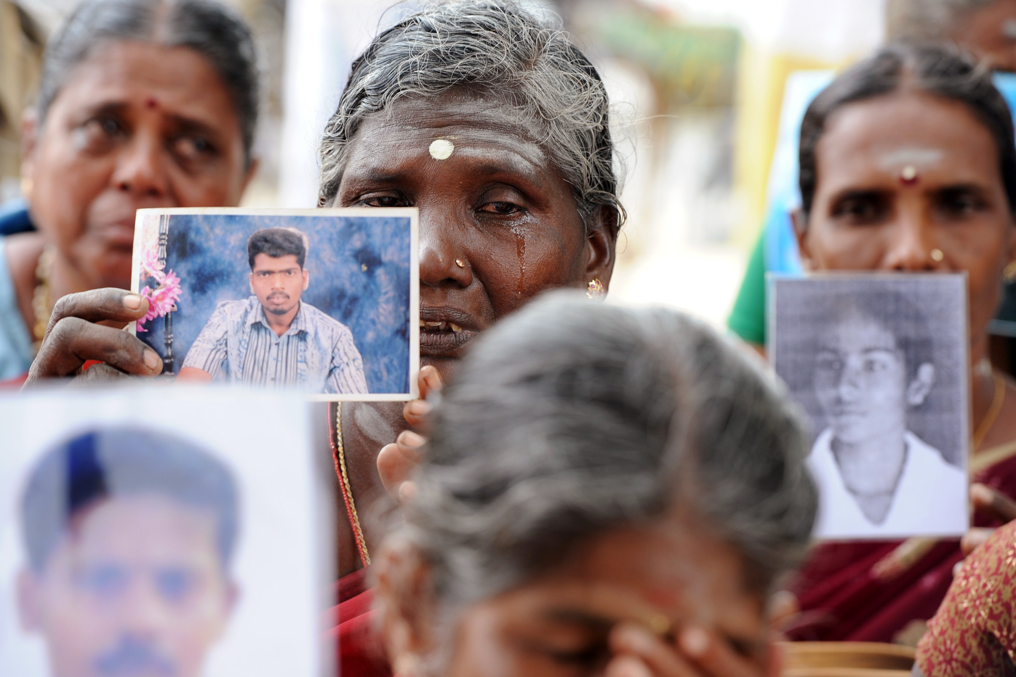 "Sri Lankan mothers from the ""Dead and Missing Person's Parents"" organisation hold photographs as they takes part in a protest in Jaffna, some 400 kilometres (250 miles) north of Colombo on November 15, 2013. British Prime Minister David Cameron is flying to Jaffna, which bore the main brunt of the fighting, to meet victims of a war which raged for 37 years.  AFP PHOTO/LAKRUWAN WANNIARACHCHILAKRUWAN WANNIARACHCHI/AFP/Getty Images"