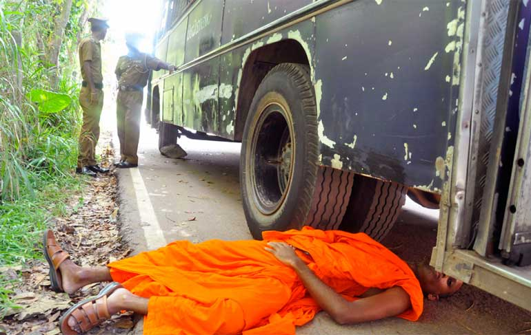 Monk protests under the prison bus