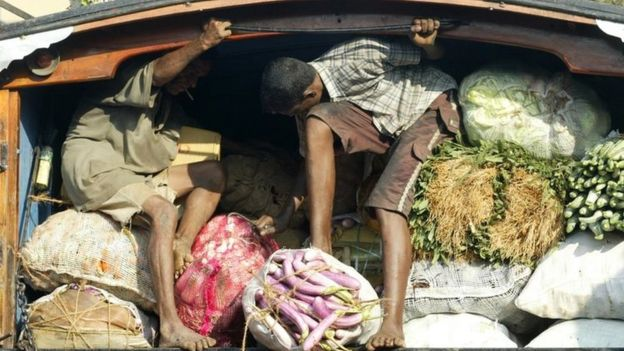 Two men ride on back of open truck, whilst holding in food produce for sale at market stall in Colombo.