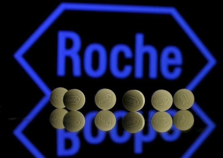 Roche tablets are seen positioned in front of a displayed Roche logo in this photo illustration