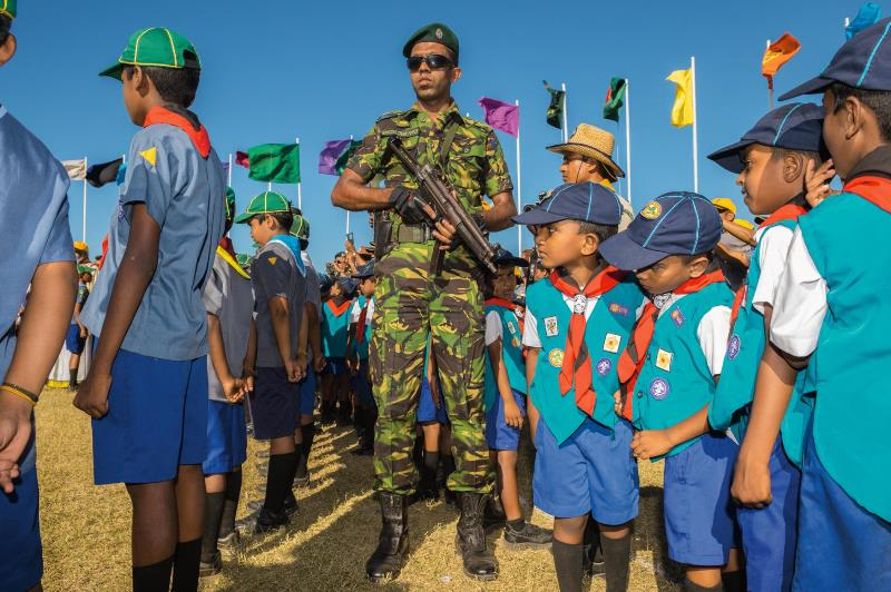 Scouts prepare to sing for the president as a policeman in his security detail stands watch. The national jamboree was held this year in Jaffna, the first time it has been in the Northern Province.