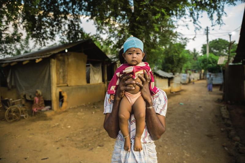 At a camp for displaced Tamils, a man hides behind his child. The memory of the war, which ended in a bloody attack, looms large. Tens of thousands of Tamils are still waiting to be resettled.