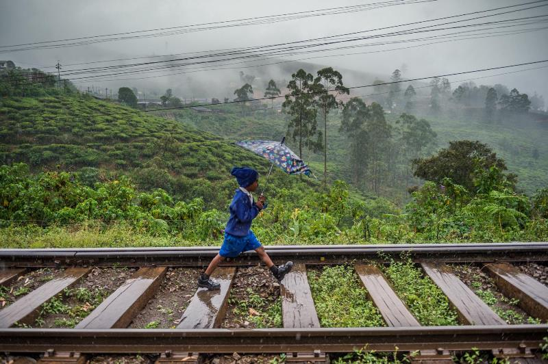 A student strides home from school on the railroad tracks near the station in Nanu Oya. The British colonial government built the railway to transport coffee and later tea from the hill country in the Central Province to Colombo